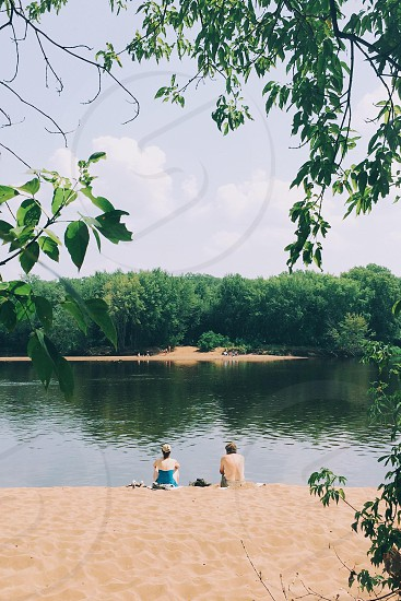 man and woman sitting on shore line photo