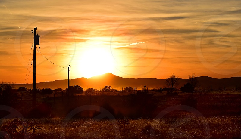 Sun setting behind the mountains in rural northern New Mexico. photo