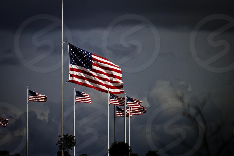 american flags on grey poles against dark grey cloudy sky photo