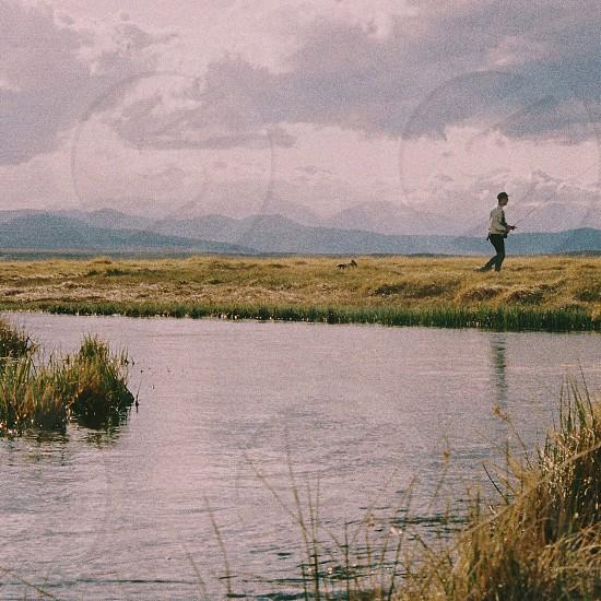 man walking near the lake photo