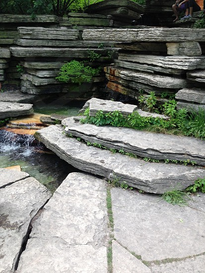 Nature at it's finest rocks with plants and small waterfall. The hidden beauties of the city. photo