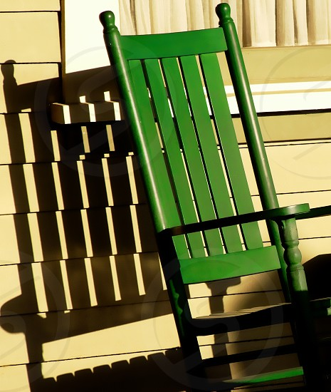 Green wooden rocking chair throws a dark shadow on a yellow house photo