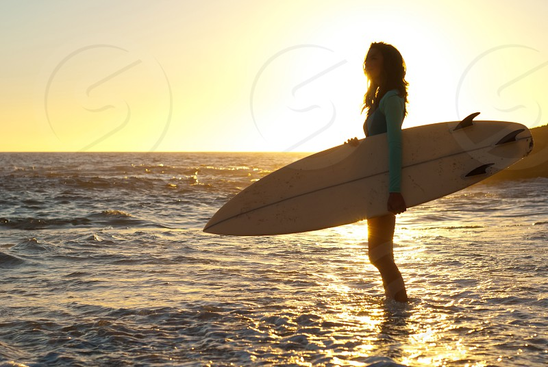 Woman young woman surfer surfboard sunset silhouette wetsuit beach ocean waves rocks long hair Pacific Ocean Southern California photo