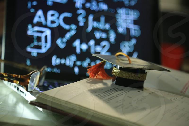 graduation moments concept study and proud moments mathematics book graduation cap and a happy graduated finger photo