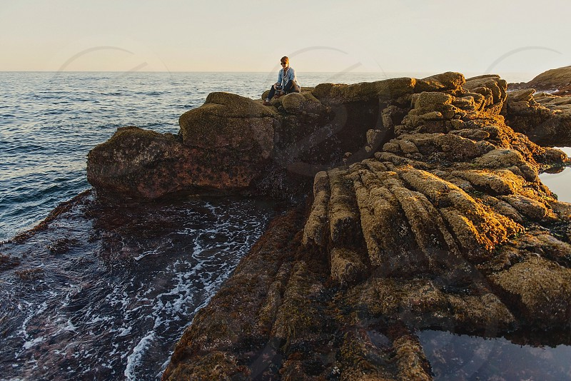 woman sitting on a brown sea rock cliff overlooking the water photo