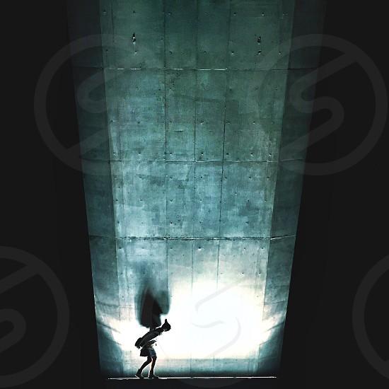 person walking next to gray wall photo