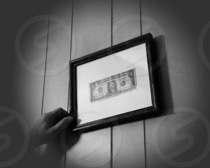 black frame wall mounted dollar photo