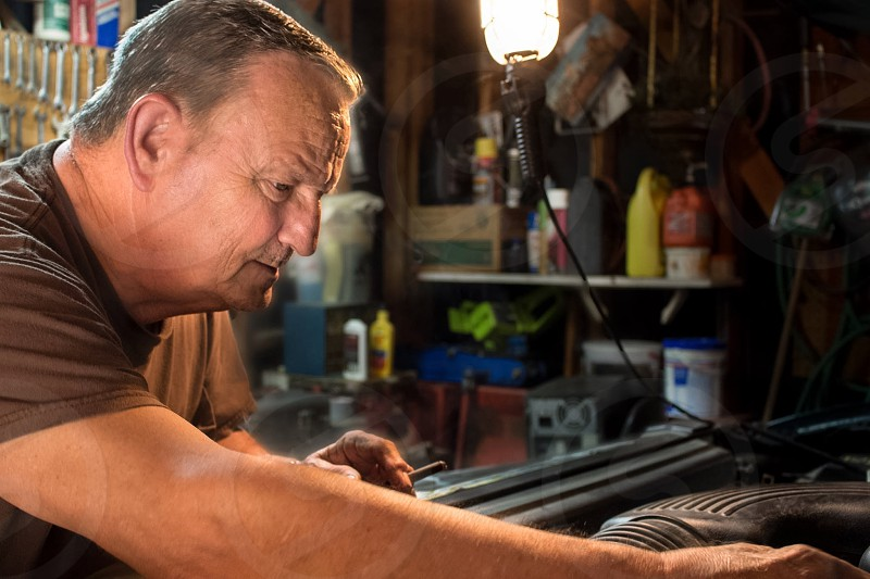Mature man doing basic checkups on his truck in his garage. photo