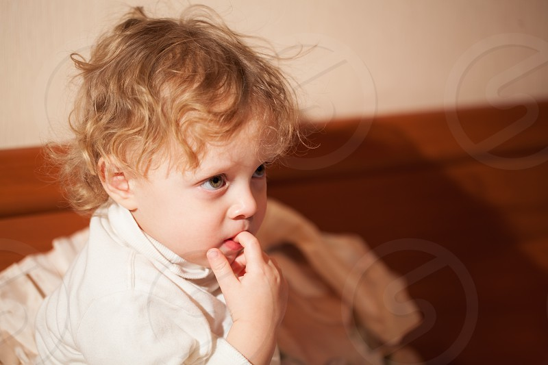 Adorable thoughtful little child with curly blond hair sitting chewing a finger and staring ahead with a pensive expression watching cartoons on tv photo