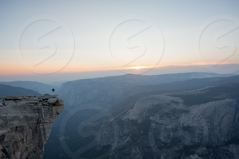 A daring jump at the top of Half Dome in Yosemite National Park during sunset. photo