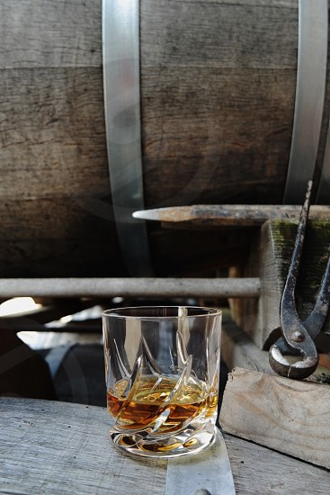 a glass of whiskey on a barrel photo