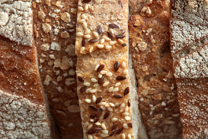 Rustic bread. Macro photo of fresh bread slices with sesame seeds and flax. Healthy food. Flat lay photo