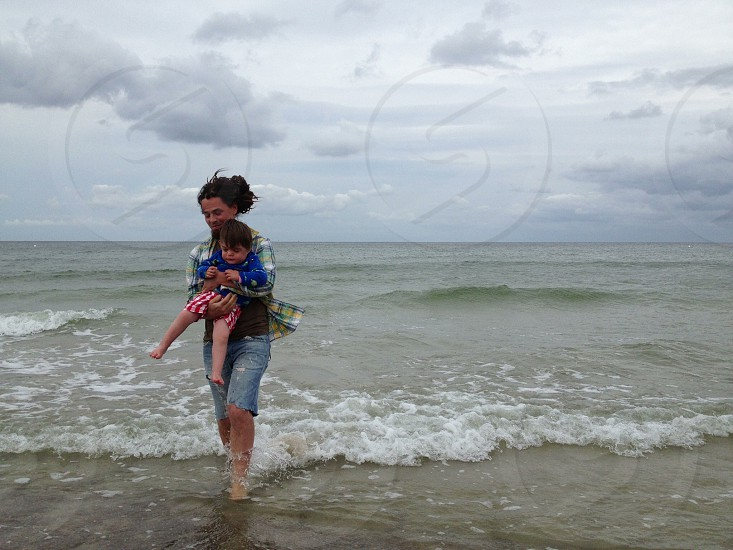 woman holding baby in shallow beach water photo