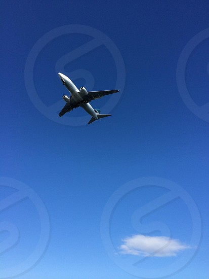 Single Airplane flying overhead in blue sky.  photo