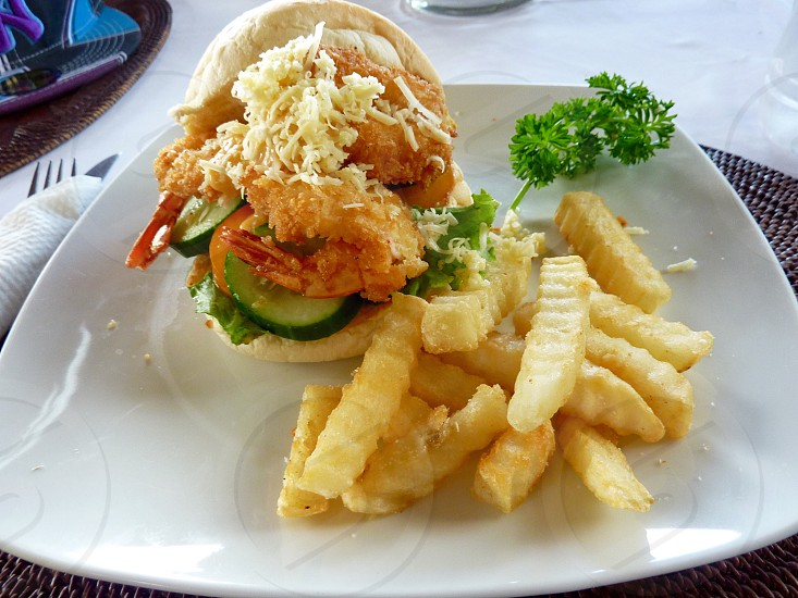 shrimp with cucumber sandwich beside potato fries on square white ceramic plate photo