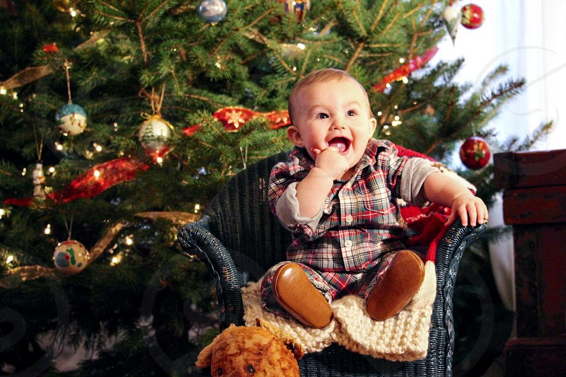 baby's brown and grey checked dress shirt seating on b lack fabric sofa chair near green christmas tree photo