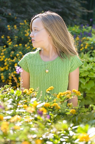 Girl in green with flowers and sun photo