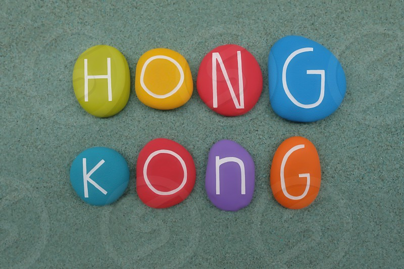 Hong Kong special administrative region on the eastern side of the Pearl River estuary in southern China. Souvenir composed with multicolored stones over green sand photo