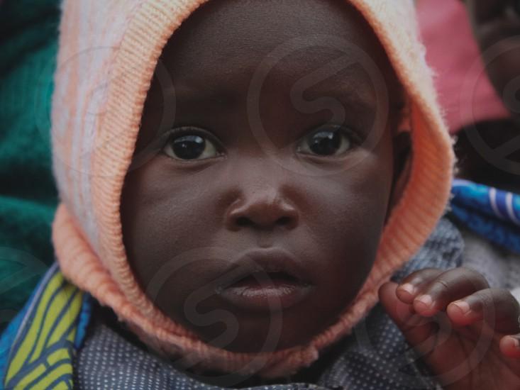 child wearing orange white knit cap in closeup photo