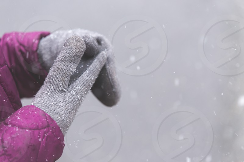 A young girl's grey mittens during a snow storm photo
