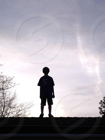 boy standing on rooftop view photo