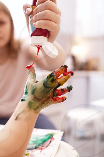 Young child playing with finger paints holding out its hand as the mother applies bright orange paint from a tube photo