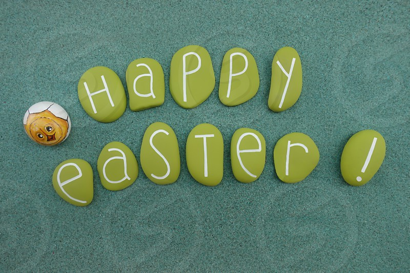 Happy Easter message with a composition of green colored stones ove a green sand and a stone design                  photo