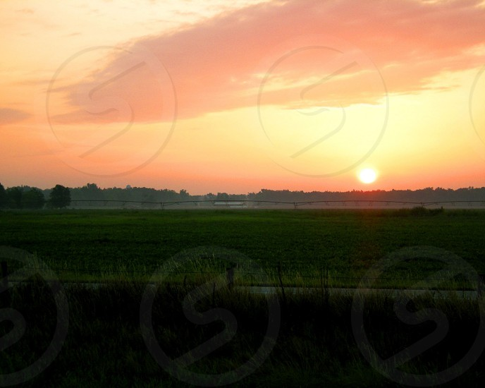 Farm equipment and sunrise over rice field photo