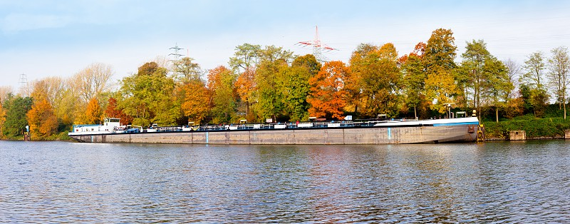 German freight ship anchoring on canal in fall-colored landscape Germany central Europe photo