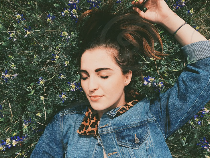 woman with brown hair in grass eyes closed in jean jacket with cheetah collar photo