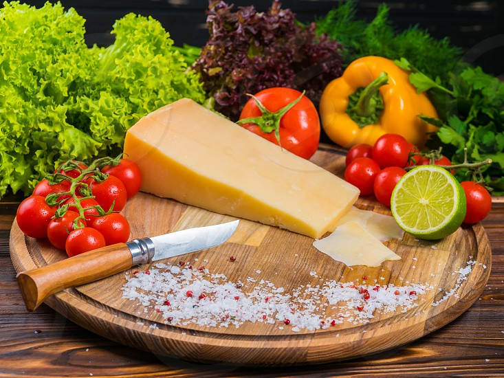 wooden board with parmesan cheese fresh cherry tomatoes lettuce sea salt and red pepper. The knife for cutting vegetables. Appetizing still life from vegetables photo