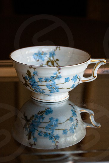 Reflection of bone china teacup in silver tray photo