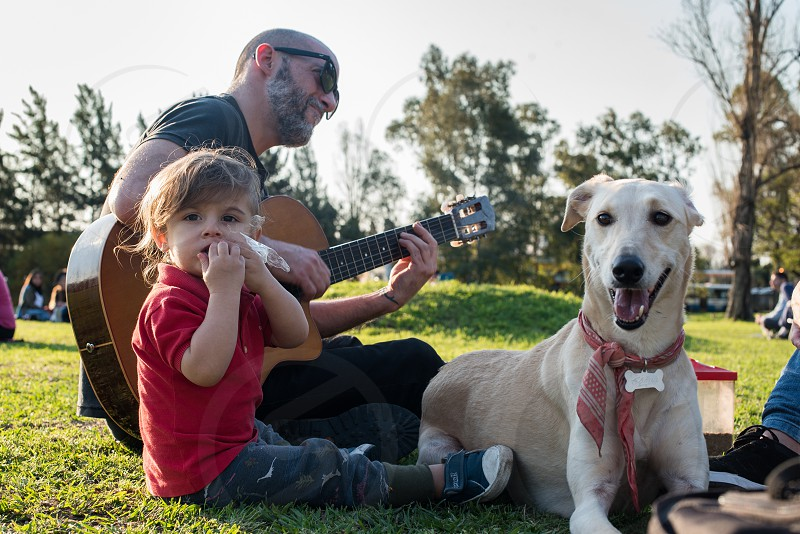 toddler boy looking at camera at park with dog next to him sitting down and eating while hipster father adult man playing guitar at sunset at spring photo