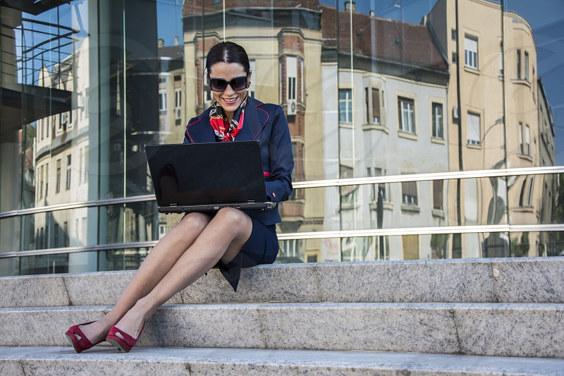 Pretty female attorney inside of a courthouse sitting on stairs and finishing work on laptop photo