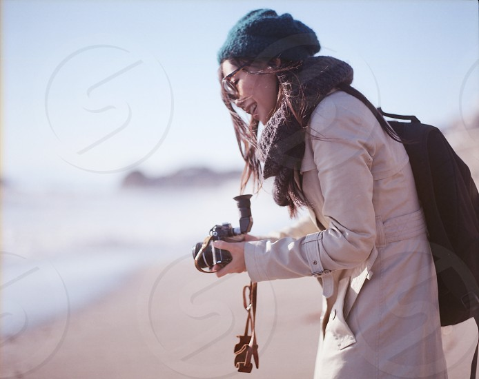 woman in brown coat holding a camera photo