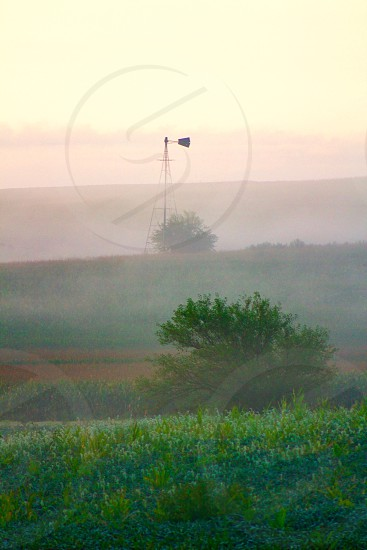 Early morning mist on terraced farmland with windmill against a light pink sky  photo