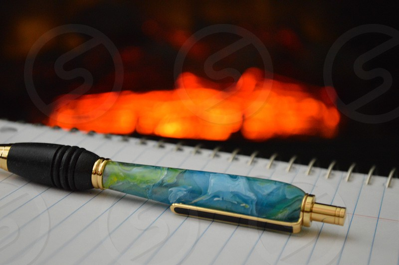 blue and black click pen on white spiral notebook photo