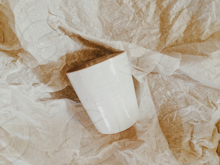 white ceramic cup and beige textile photo
