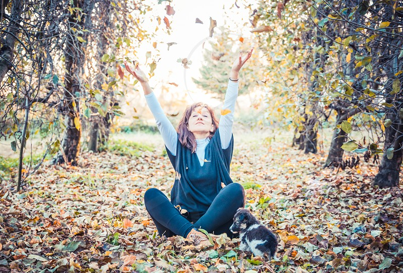 Young Happy Woman Playing With Dry Leaves In An Autumn Park photo