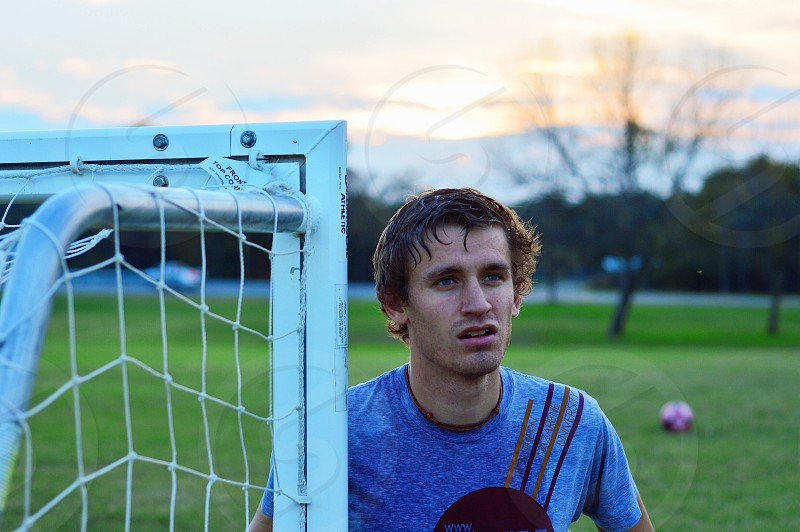 Soccer player training at dusk looking hopeful.  photo