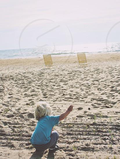 child wearing blue t-shirt squatting on sandy shore during daytime photo