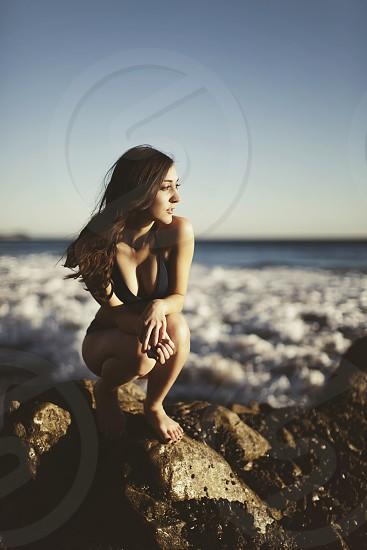 woman sitting on stone photo