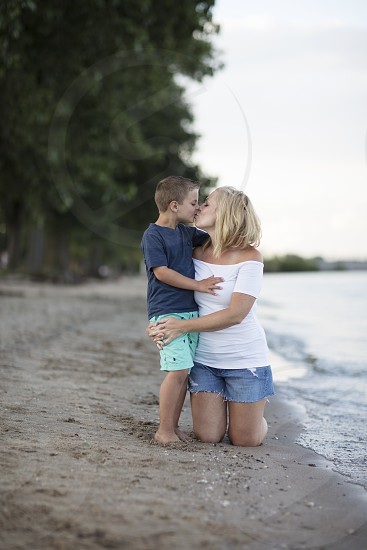 A mom and her son giving her a kiss on the beach photo
