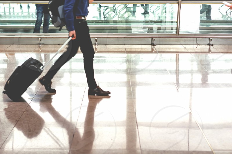 Traveler pulling suitcase in modern airport terminal. Travel and transportation concept photo