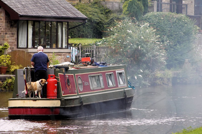 polluting the air on the waterway canal dog Man barge   photo