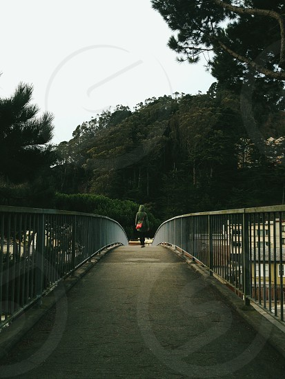 view of women wearing gray cardigan on the bridge with background on forest photo