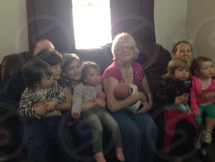 people carrying kids sitting on couch photo