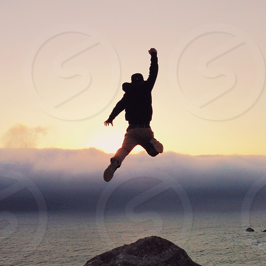 man jumping on cliff photo photo
