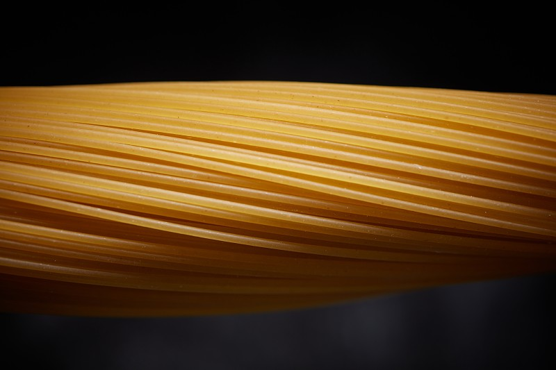 Close-up of a bunch of raw yellow spaghetti on a black background. photo