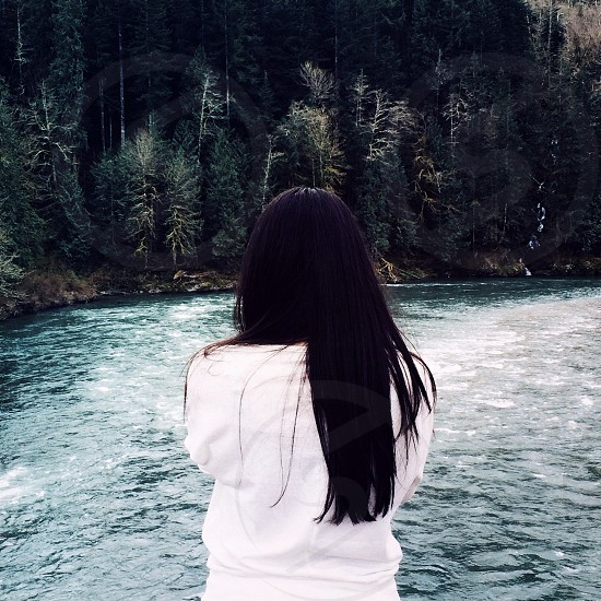 brunette woman in white standing over blue mountain river photo